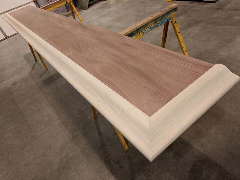 solid Sapele mahogany slab trimmed with our maple BR475 Bar rail molding